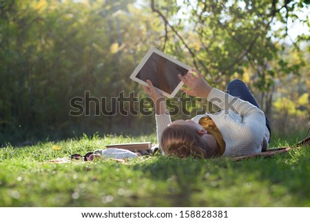 woman lying on bedding on green grass with tablet during picnic in the park