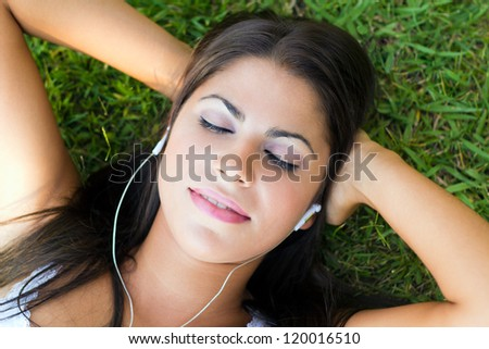 Woman lying on grass listening to music outdoors