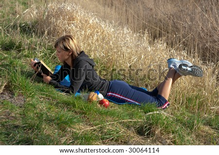 Woman lying on grass reading a book.