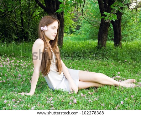 Woman lying on grass sown with flowers and holding a flower