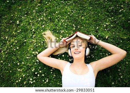 Woman lying on grass with book and headphones