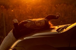 Woman lying on her back in a vehicle at golden twilight hour. Rural landscape and dramatic sky at dusk. Rural photography scene. Photographic model at the golden hour. Natural beauty.