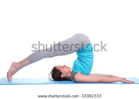 Woman lying on her back on an exercise mat in a yoga position feet over her head, isolated on a white background.