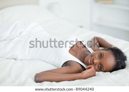 Woman lying on her back with a knowing smile in her bedroom
