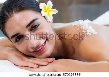 Woman lying on massage table with salt scrub on back at spa