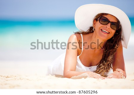Woman lying on sand at the beach and smiling