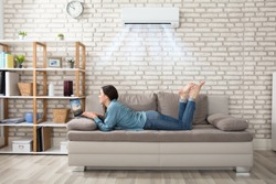 Woman Lying On Sofa Using Laptop Enjoying The Cooling Of Air Conditioner At Home