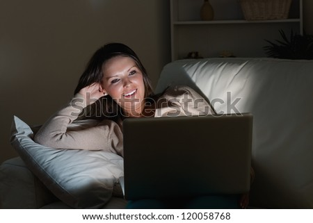 Woman lying on sofa with her laptop in night in the living room