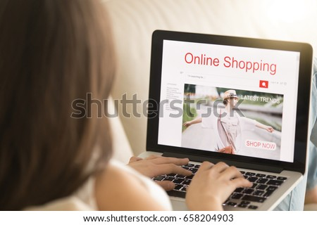 Woman lying on sofa with laptop pc visits apparel store web page in Internet. Female customer shopping trendy clothes. Girl buying elegant wear on seasonal sale online. Close up view over the shoulder #658204903