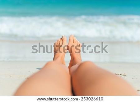 Woman lying on the beach. Legs.
