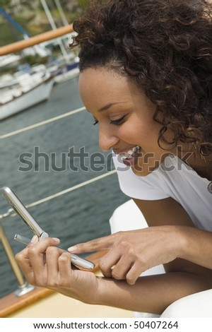 Woman lying on yacht, using mobile phone, (close-up)