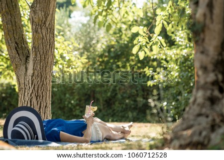 Woman lying relaxing in the shade of a tree in a  garden  in summer with a glass of water in her hand. #1060712528