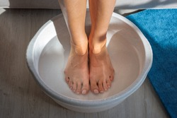 Woman made bath with hot water and baking soda for his feet. Homemade bath soak for dry feet skin