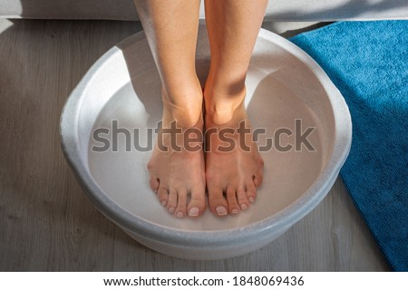 Woman made bath with hot water and baking soda for his feet. Homemade bath soak for dry feet skin Stock photo ©