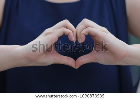 woman make her hand in heart shape at the position of her heart with hear blue shirt #1090873535