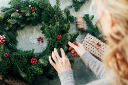 Woman makes a fir wreath for advent. Christmas Eve and crafting decorating. New Year celebration.