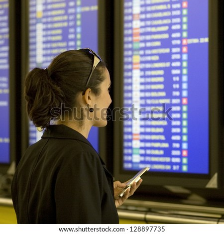 Woman makes check-in with smartphone at airport - stock photo