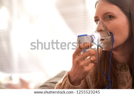 woman makes inhalation nebulizer at home. holding a mask nebulizer inhaling fumes spray the medication into your lungs sick patient. self-treatment of the respiratory tract using inhalation nebulizer Foto stock ©