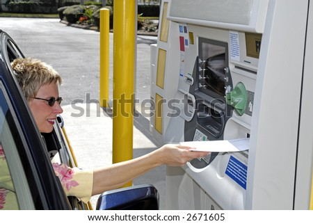 Woman making a deposit at a drive up ATM.
