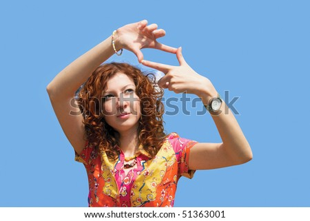 Woman making a frame of their hands. Girl has red wavy hair