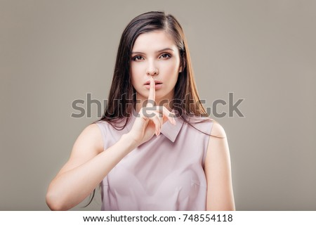 Woman making a hush gesture with her index finger on lips.