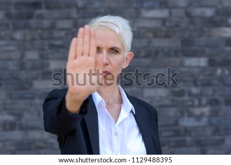 Woman making a stop or halt gesture with her hand in a front view focus on face