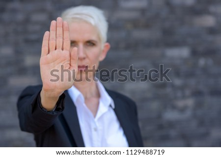 Woman making a stop or halt gesture with her hand in a front view focus on hand