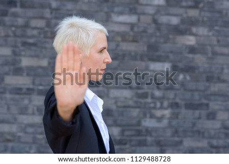 Woman making a stop or halt gesture with her hand in a side view focus on face
