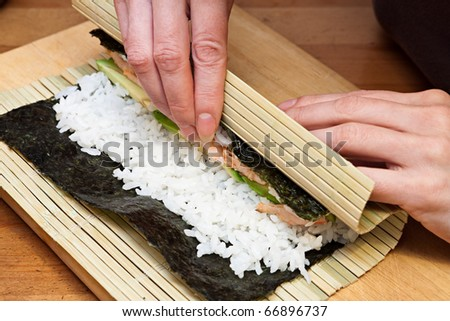 Woman making at home Japanese sushi rolls.