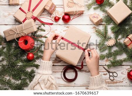 Woman making beautiful Christmas gift at table Foto stock ©