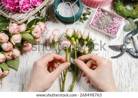Woman making bouquet of pink roses. Florist at work.