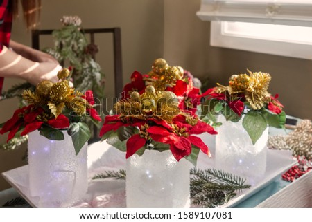 Woman making Christmas crafts with painted jars and poinsettias in her home. Wearing a red plaid shirt and a red plaid bow.