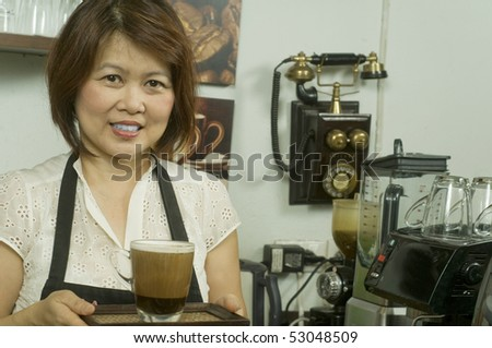 Woman making coffee in restaurant