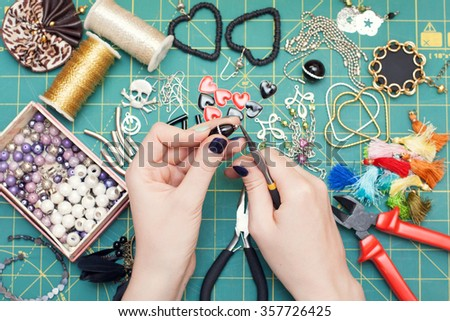 Woman making costume jewelry, earrings. Home made. Tools. Top view. Work place.