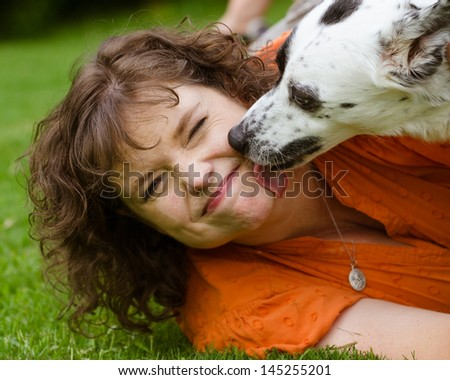 stock-photo-woman-making-disgusted-face-while-being-licked-by-her-pet-dog-145255201.jpg