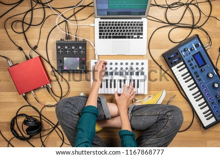 Woman making electronic music on laptop computer and digital instruments. Top view of young female producing modern indie music on synthesizer and digital controllers #1167868777