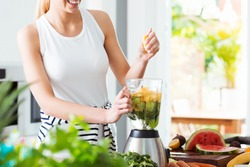 Woman making fruit cocktail in kitchen during cleansing detox diet to boost energy