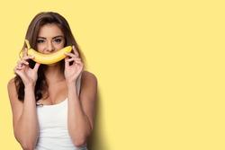 woman making fun with a banana. yellow background
