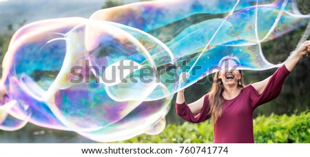 Woman making giant soap bubbles in a park.