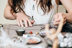 Woman making handmade gemstone jewelry, home workshop. Artisan woman creates jewelry. Art, hobby, handcraft concept