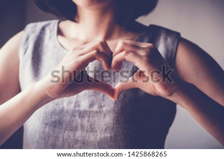 Woman making hands in heart shape, heart health insurance,social responsibility, gratitude,donation, happy charity volunteer concept, world heart day, International Day of Sign Languages, organ donor