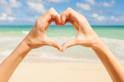 Woman making heart shape on the beach.