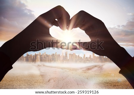 Woman making heart shape with hands against path in yellow field leading to city