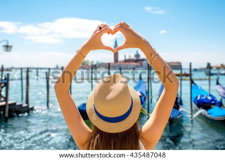 Woman making heart shape with hands on the beautiful view in Venice. Venice is one of the favorite tourist city