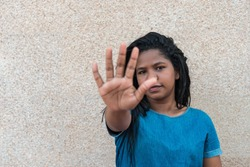 Woman making NO or STOP gesture with hand, stop drugs, stop violence against children, stop violence against women, human rights violations, human trafficking.