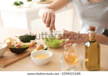 Woman making nourishing mask with avocado in kitchen