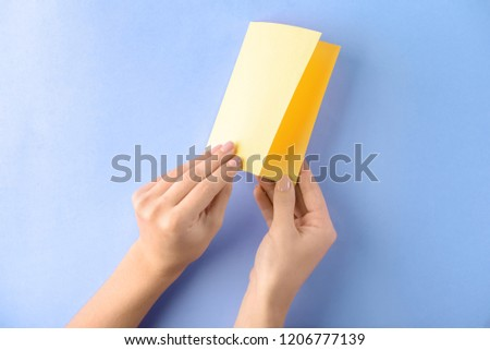 Woman making origami boat on color background #1206777139