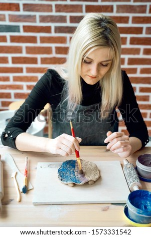 Woman making pattern on ceramic plate with paint brush. Creative hobby concept. Earn extra money, side hustle, turning hobbies into cash, passion into a job, vertical #1573331542