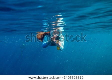 Woman making photo underwater. Girl snorkeling in full-face mask. Snorkel with fish under water surface. Snorkeling gear. Action camera. Active vacation by tropical seaside. Diving girl in open water #1405528892