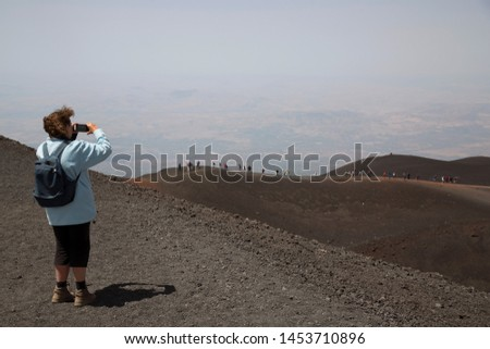 woman making picture of mass tourism on the secondary summit of Mount Etna, big tourist groups of people walking around the crater